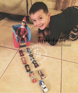 Elf on the shelf in toy truck with matchbox cars leading the way. Easy Elf on the shelf ideas.
