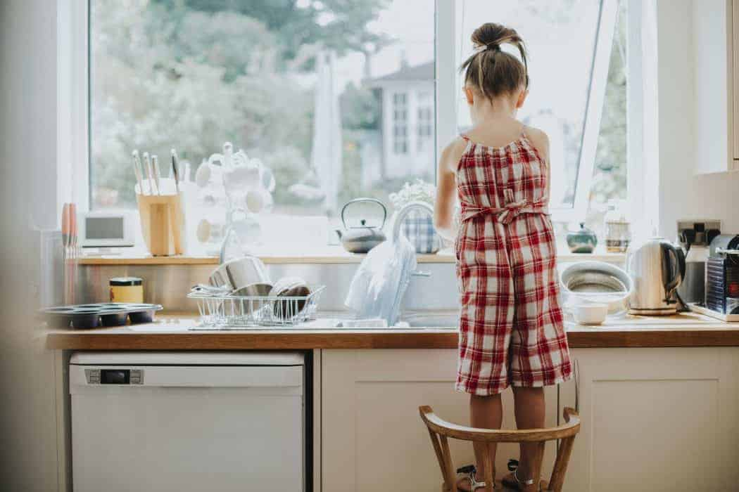 little girl doing her chores by washing the dishes.