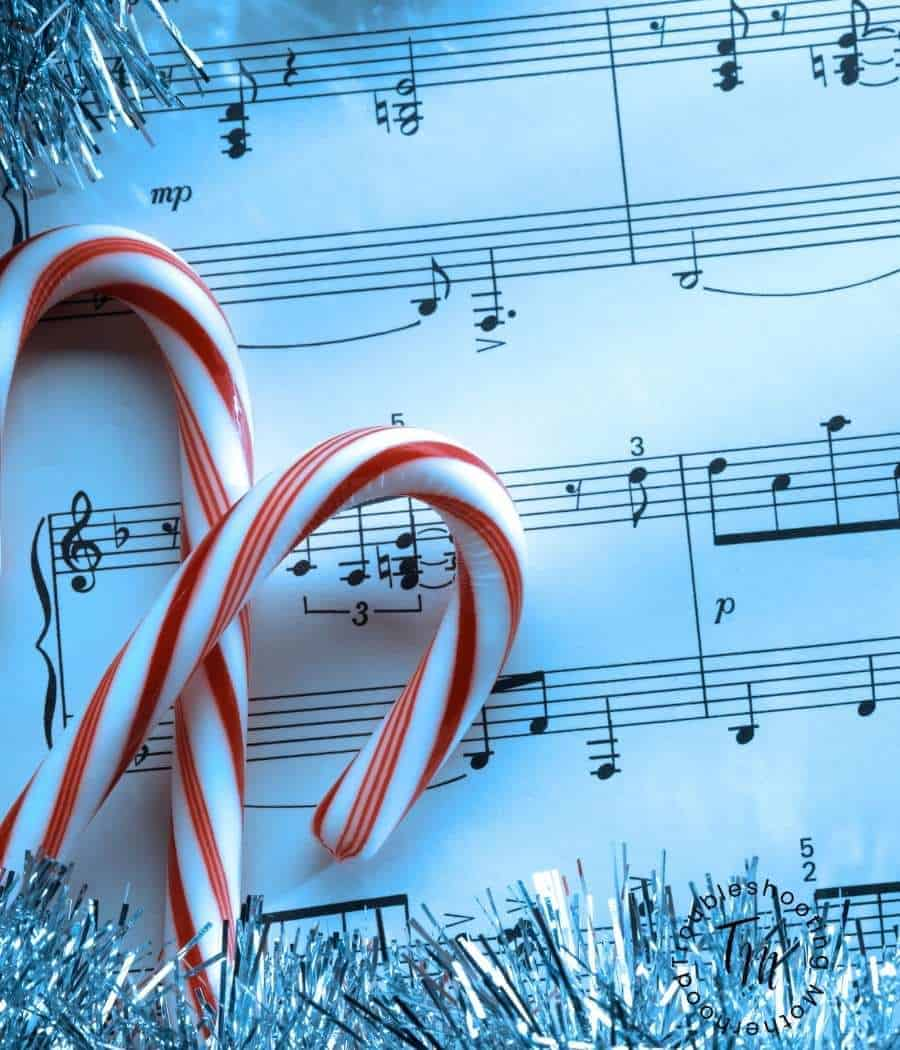 A sheet of Christmas music with candy canes on top. Fun tradition of listening to Christmas music as a family.