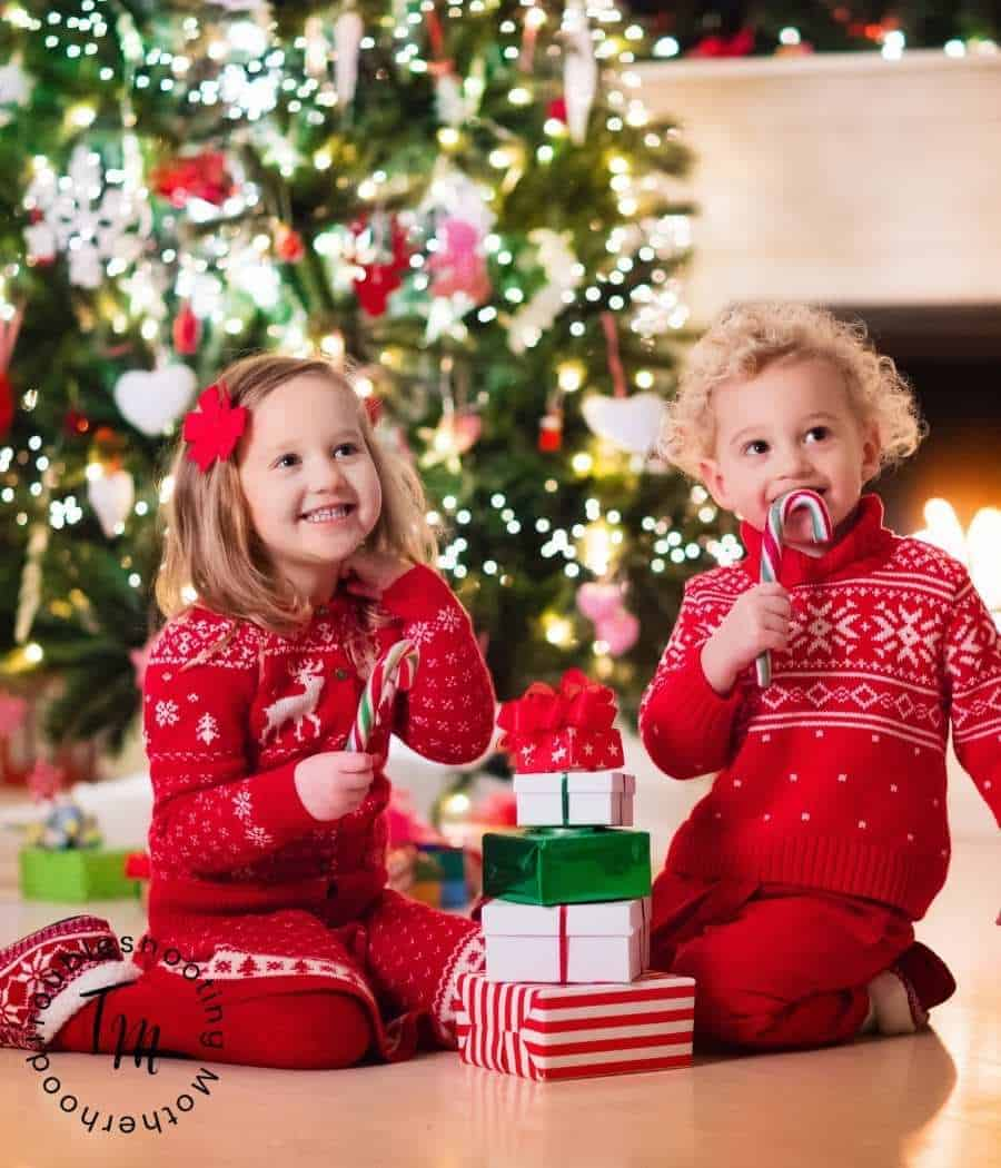 Siblings in matching outfits sitting in front of a Christmas Tree.