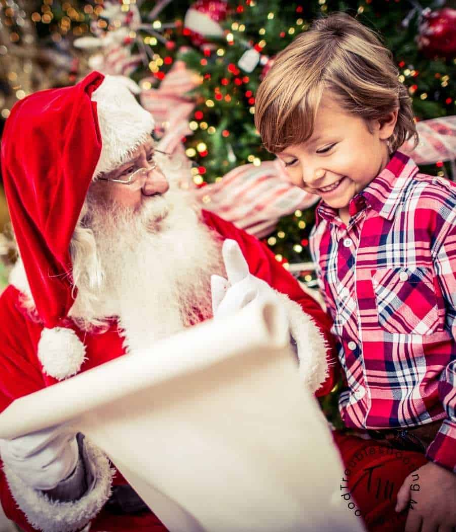 A little boy visiting with Santa Claus.